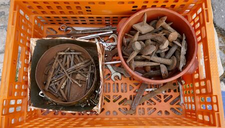 Old rusty nails and hand tools in a rusted metal and a plastic bowl inside a orange plastic container Stok Fotoğraf