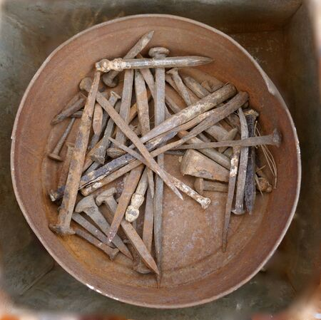 Old rusty nails and hand tools in a rusted metal bowl