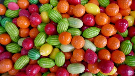 Delicious fruit sweets. Colorful fruit dragees, orange, melons, cherries, lemons, with soft filling. Close-up.