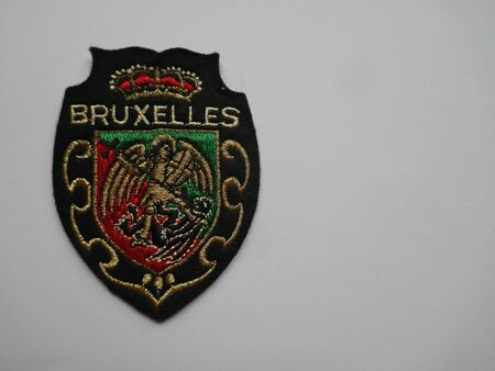 Patches, Crests, Souvenir from Belgium, Brussels, Bruxelles. Colorful, shiny and elaborately embroidered. Close-up, background, texture, isolated on white.