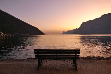 Lonely wooden bench by the lake after sunset Stok Fotoğraf