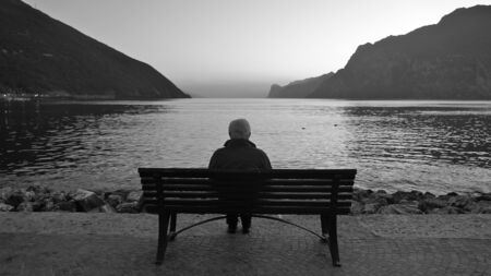 A lonely man sitting on a wooden bench at dawn before sunrise, looking at the lake and the light on the horizon.