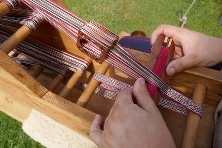 Webbed weaving loom for making narrow borders and edgings. Loom with weaving shuttle for making borders and edgings. Old craft techniques and traditional weaving art of the Vikings or Slavs in the Middle Ages. Standard-Bild