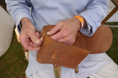 Saddler. Leather craftsman at work. He sews a bag by hand. Close-up.