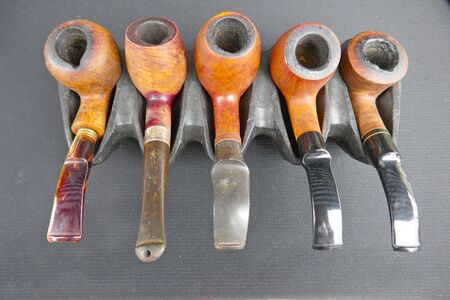 Five old tobacco pipes in a pipe rack
