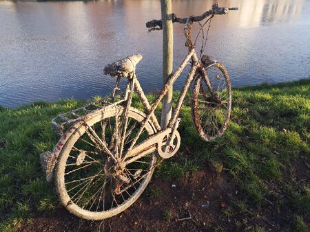 Old rusty bike was pulled out of the water and leaned against a log on the banks of a river. It lay in water for a long time and is covered with mud and shells.