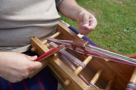 Webbed weaving loom for making narrow borders and edgings. Old craft techniques and traditional weaving art of the Vikings or Slavs in the Middle Ages.