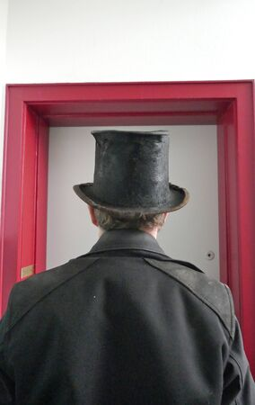 Chimney sweep stands in front of a front door in work clothes. Rear view.