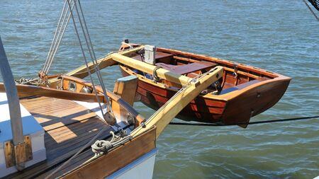 Dinghy, small rowing boat, made of mahogany wood, attached to the stern of a vintage sailing yacht. Schleswig-Holstein, Germany Zdjęcie Seryjne