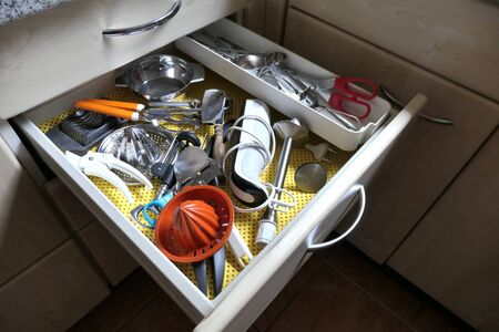 Many kitchen utensils in an open drawer. View of an open drawer with many household items in a kitchen. Zdjęcie Seryjne