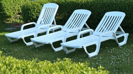 Three white plastic garden loungers stood in the garden on the lawn in front of a green hedge