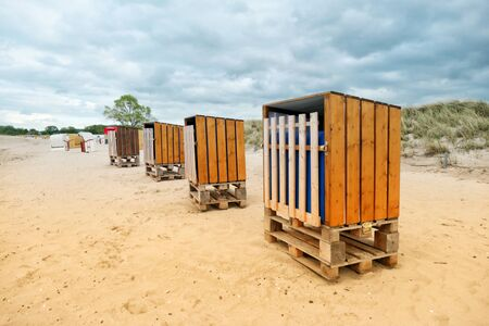 Four rustic beach chairs, from wooden boards and Euro pallets, stands in a row on the Baltic Sea beach in Schleswig-Holstein, Germany.