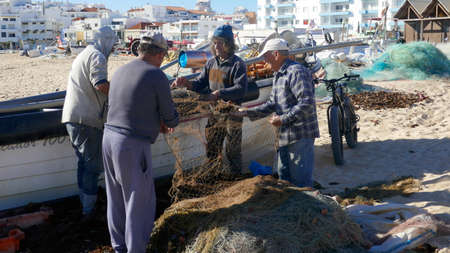 Armacao de Pera, Algarve, Portugal - March 4, 2019: Fishermen mending their nets. At the long, wide, fine sandy fisherman beach