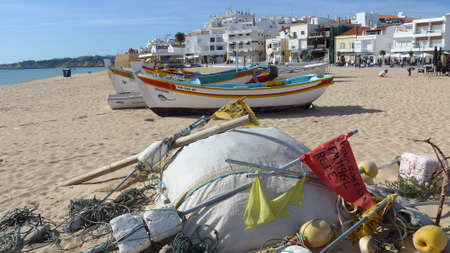 Armacao de Pera, Algarve, Portugal - March 14, 2019: Many buoys and accessories for fishing in front of typical Portuguese, colorful fishing boats on the beach.