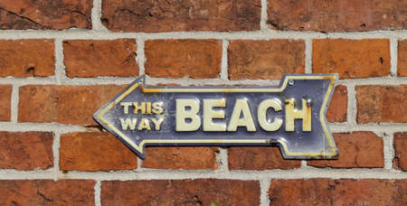 This way beach. Old rusty metal sign on a red brick wall. Blue with white lettering. Path to the beach, signpost and tin sign with an arrow pointing to the left. Zdjęcie Seryjne