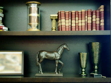 statuettes: Shelves with books, statuettes and frame for photos in the office Stock Photo