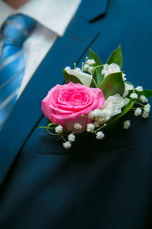 Beautiful little bouquet of red and white flowers in the pocket of the groom in wedding day
