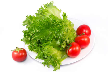 Red tomatoes and green lettuce (Common Lettuce) on a white plate and isolated on white background. Natural vitamins in the spring and summer season.