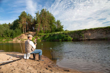 Fishing on the river in a rural place on a summer day. A man with a fishing rod sitting by the river. Sunny day. Beautiful white clouds in the blue sky. A beautiful rural landscape. Stock Photo