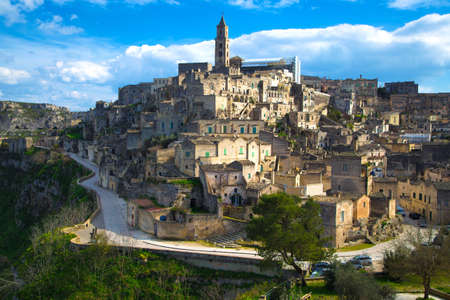 Beautiful cityscape of Matera against the blue sky. Large white clouds in the sky. City in the rock. The winding road around the city. Green grass and trees. Italy.