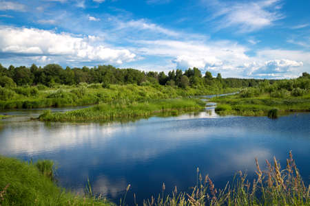 Beautiful summer rural landscape with a river. Clear blue sky with white clouds. In the river reflected clouds. Beautiful lush green vegetation along the winding shores. The summer season for fishing.