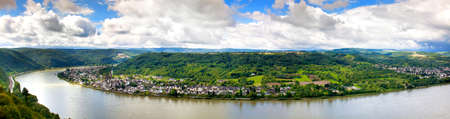 Panorama of the urban landscape on the Rhine river. A small town along the river Bank surrounded by low mountains. A lot of green vegetation. Beautiful lush vegetation. Blue sky with white clouds.