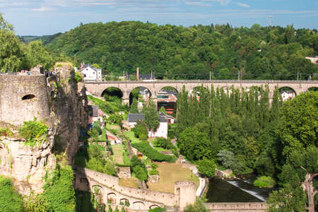 Beautiful old part of Luxembourg city. State (Grand Duchy) in Western Europe. Large old houses, an old bridge and stone towers. A lot of green trees. Summer season