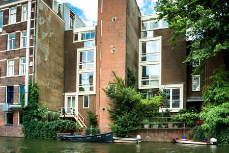 Red brick houses and green vegetation near the canal. Large glass Windows. Many boats on the water near the houses.. Amsterdam. Urban landscape. Summer season. Blue sky with white clouds. Archivio Fotografico