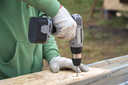 A man drills holes in the Board with a drill.  White utility gloves on his hands. Construction of a house in a rural area . Close-up