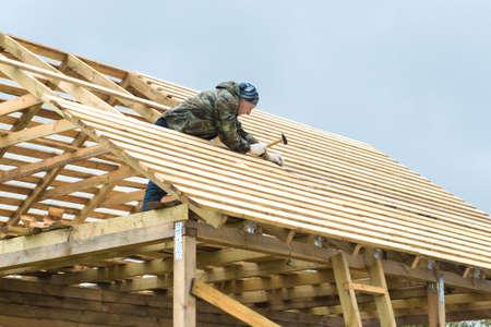 Bau eines Holzhauses in ländlicher Umgebung. Die Konstruktion des Daches. Erwachsene Männer, die mit dem Bau beschäftigt sind. Werkzeuge in ihren Händen. Bewölkter kühler Tag.