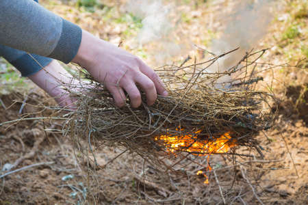 Safely lighting a fire in the forest countryside. Rural place. Dug a fire pit. Hands making a fire Stock fotó