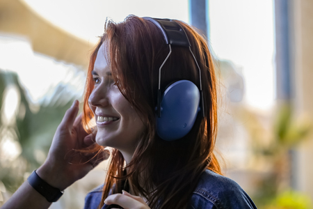 Beautiful red-haired woman puts on antinoise headphones, preparing to fly a helicopter Stock Photo