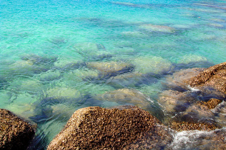 wallpaper of clear blue tropical sea water with rocks under surface 免版税图像