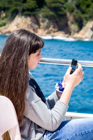 A young girl with long hair looks into the phone while sitting on a pleasure boat.