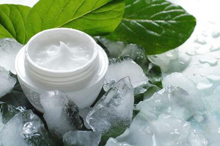 A jar of a cosmetic cream with fresh green leaves and pieces of ice. Beauty concept.