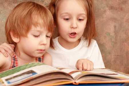 girl and boy friendly reading an interesting book Stock Photo - 4308612