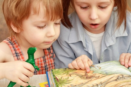 girl and boy friendly reading an interesting book Stock Photo