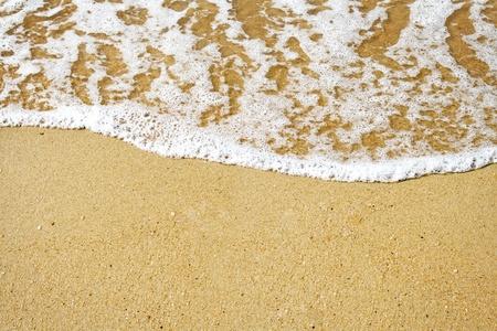 Sandstrand und schaumige Brandung