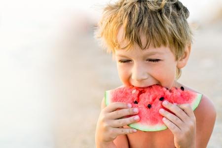 boy taking a bite of watermelon Standard-Bild