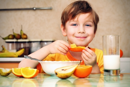 1 boy only: boy, breakfast, drinks milk, eats cereal and orange Stock Photo