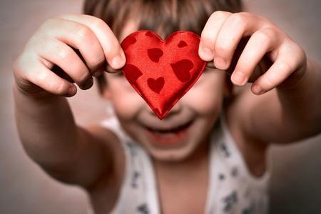 corazon en la mano: dos manos sosteniendo un coraz�n rojo Foto de archivo