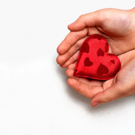 hands holding heart: two hands holding a red heart