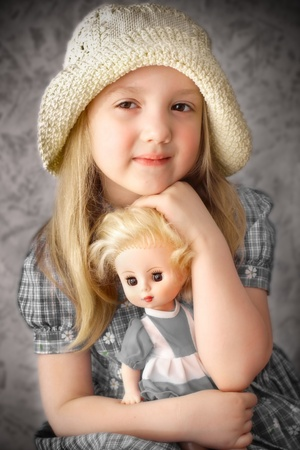 pretty girl holding a doll, an old photo