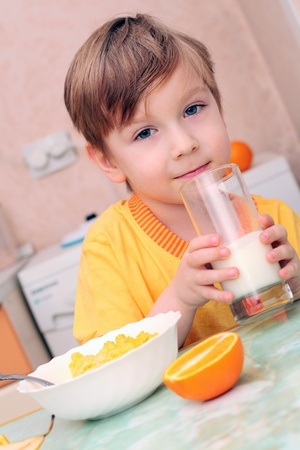 one boy only: boy, breakfast, drinks milk, eats cereal and orange Stock Photo