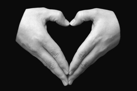 pair of hands in the form of heart on a black background Stock Photo - 10840456
