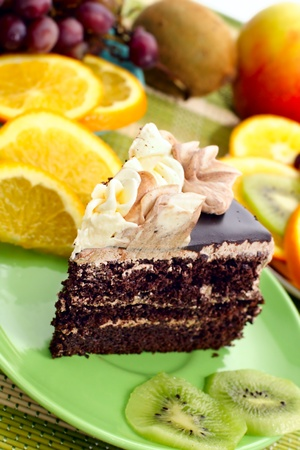 chocolaty: Birthday cake with cream with fruit in the background Stock Photo