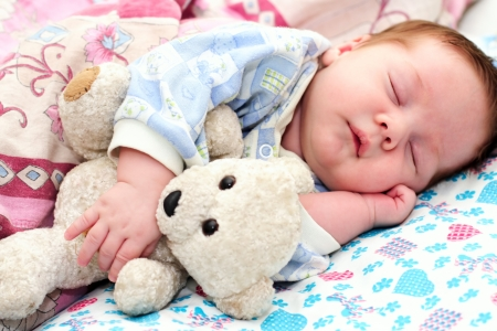 portrait of a sleeping baby with a toy photo