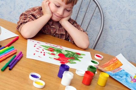 art activity: boy paints a Christmas picture