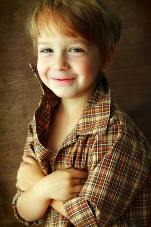 portrait of a beautiful boy on a brown background photo