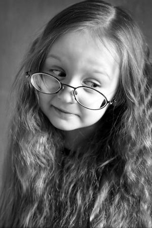rubia ojos azules: niña con pelo largo con gafas, buscar Foto de archivo